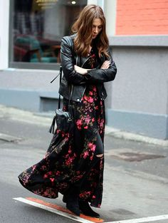 Street style look com vestido longo floral sobre calça preta e botas.