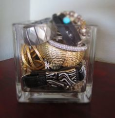 Great idea to repurpose a vase as a jewelry holder.  Also a pretty display on top of a dresser!