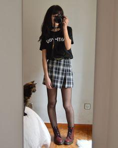 look grunge para os dias de calor com saia xadrez , camisa , coturno e meia calça .