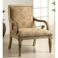 Lend your space a touch of French charm with this fun wooden padded accent chair that has a unique scrolled arm design and is made from solid wood with a whitewash finish. Its upholstered print features French words in a fancy script.