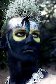 interesting face paint, especially the eyes. Still masculine.
