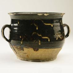 Posset pot  Pot with two handles thrown in buff body with dark brown slip two thirds way down with white interlaced motifs around body and rim which has been absorbed in the slip  18th century Staffordshire or Derbyshire  Acquired 1931 Greenslade 17.5 cm high Mark:  c587