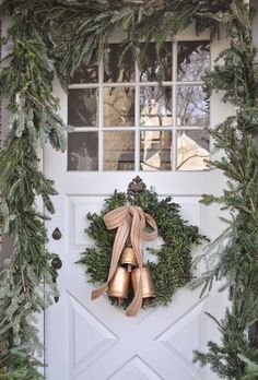 a lush evergreen garland to frame the font door and a wreath with bells to match the look
