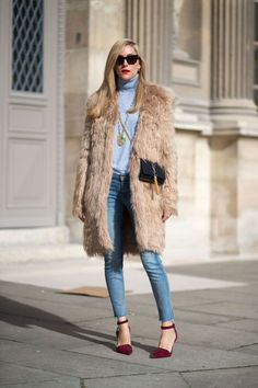 Joanna Hillman in a fur coat, baby-blue top, skinny jeans and oxblood ankle-strap heels.
