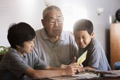 Asian grandfather and grandsons looking at photo album