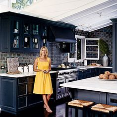 Deep green-black paint and custom tile in shades of green, gold, and turquoise lends an edge to this refined yet playful kitchen | Coastalliving.com