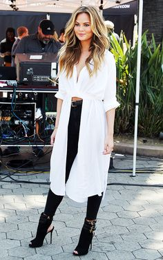 Chrissy Teigen in a white maxi blouse, high waisted black jeans, and black booties