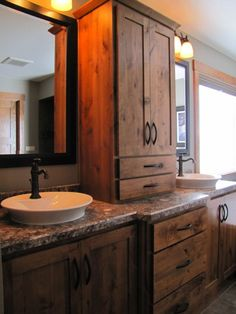 bathroom double vanity ideas using rustic wood cabinets and tower cabinet with antique pull handles between large wooden frame mirror under sconce wall lamp