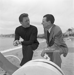 American actor Kirk Douglas, wearing a turtleneck sweater and smoking a cigarette while talking to another man on the Lido beach, Venice 1953.