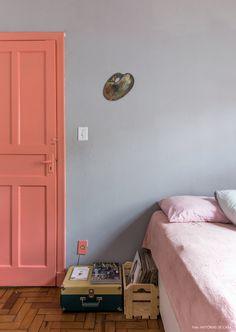 A dona desse quarto adora rosa, por isso investiu nessa cor na pintura da porta e acessórios como a roupa de cama.