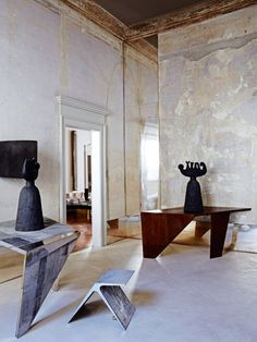 House tour: a Milanese palazzo beautifully stripped back to its roots: In the entrance hall, tables and 'DC1402A' stool by de Cotiis; plaster prototypes of brass sculptures by Massimo Campigli (1950s).