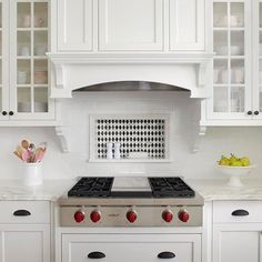 Backsplash Storage Niche A subway tile backsplash surrounds a rectangular niche that provides convenient storage for cooking necessities. The black-and-white diamond pattern in the niche adds subtle variation to the otherwise white kitchen but still blends with the room's traditional styling.
