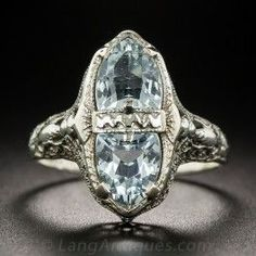 A pair of shield shape aquamarines shine back-to-back in this strikingly distinctive Depression-era (circa 1930s) Art Deco jewel, die-struck and hand-finished in fanciful 14K white gold filigree by the noted American jewelry manufacturer - Belais Bros. 3/4 inch long and lovely, Currently ring size 6 1/4+.