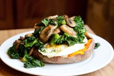 Easy baked sweet potato topped with eggs, kale, mushrooms, and onion!