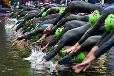 Triathlon competitors dive at the Hyde Park upon start of the women's triathlon event