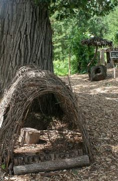 nature play...  made with twigs, or plant sunflowers in shape to tie in as they grow, to be near the garden...   Think of need for shade and bugs...  Maybe a canopy of an old curtain would be more feasible...FIN IDEA FOR KIDS WHEN CAMPING