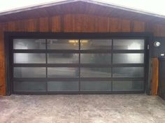 Glass single garage door. Modern with black frame and semi translucent glass panels.