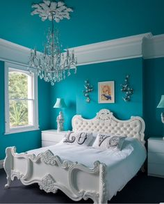 Teal walls, white Rocco  bed, crystal chandelier, bedroom
