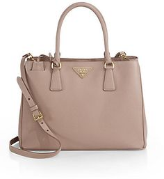 """Prada Saffiano Medium Tote A signature style in luxurious saffiano leather accented with a logo emblem. ;Double top handles, 51⁄2"""" drop;Detachable adjustable shoulder strap, 161⁄2""""-181⁄2"""" drop;Magnetic snap closure;Protective metal feet;Three inner compartments;One inside zip pocket;One inside open pocket;Logo lining;13""""W X 9""""H X 5""""D;Leather;Made in Italy"""