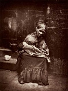 Sweeping a path across the filthy streets for a well‐dressed pedestrian could earn a few pennies, legally. Begging might make more illegally, especially if the beggar woman could use – even hire – a small child. Sometimes the children were blinded or maimed, to loosen the purse‐strings of passers‐by. Photo: Homeless woman in London, 1876-7 little Jo?
