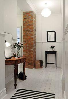 brązowa konsolka,półokragła konsolka,stylowa konsolka,czerwona cegła w korytarzu,czarny stolik,czarne lustra,prostokatne lustra,czarnobialy chodnik,paski,pasiasty dywan,pasiasty dywan,wąski przedpokój,biały przedpokój,korytarz,jak urzadzić wąski korytarz,biale ściany,skandynawski styl,nowoczesne mieszkanie,dekoracja holu,dekoracje do przedpokoju,typografie,czarny chodnik,dywan w przedpokoju,biała podłoga