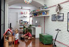 Espaço para brincar. Na última reforma, as meninas ganharam uma sala só delas (projeto do arquiteto Gil Mello), com paredes de tijolinhos e detalhes como o elefante (Coisas da Doris). Prateleiras fixadas com mãos-francesas e um baú com rodízios (Casapronta) oferecem espaço para guardar brinquedos. A luminária estampada, Vera trouxe da Califórnia.