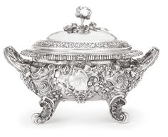 A George IV Silver Soup Tureen and Cover, Joseph Angell, London,  1820  of good weight, bombé oval, the sides applied with rococo cartouches flanked by scrolling strapwork, masks, flowers, shellwork and eagles, with leaf-capped scrolls handles and matching supports, engraved with later arms on one side, cover chased to match, rose spray finial