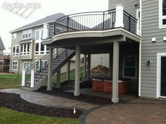 A second story deck designed with curved rail, straight stringer staircase and patio below creates a versatile and attractive outdoor space, Notice the hot tub area underneath the deck too.