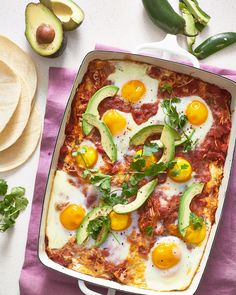 This huevos rancheros casserole is layered with corn tortillas, plenty of beans & cheese, and a tomato-chile sauce, then topped with eggs & baked.