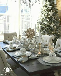 Christmas table idea with neutral, silver, and gold decor and stars for tablesca. Christmas table idea with neutral, silver, and gold decor and stars for tablescape and place settings. Flocked nature tree in the dining room with crystal chandelier Silver Christmas Decorations, Christmas Table Settings, Christmas Tablescapes, Christmas Centerpieces, Christmas Candles, Christmas Place Setting, Table Centerpieces, Diy Centrepieces, Christmas Dining Table