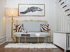 Glam sitting area: white paneled walls, animal art, gilded settee, lucite coffee table, zebra pillows + a shag rug. Home Staging, Vintage Settee, Antique Couch, Living Spaces, Living Rooms, Family Room, Sweet Home, Architecture, House Design