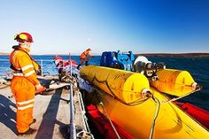 Workman preparing to tow a Pelamis P2 wave energy generator on the dockside at Lyness on Hoy, Orkney Isles