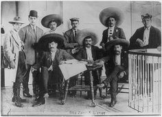 Photo shows Emiliano Zapata Salazar (1879-1919), leader of the Mexican Revolution (1910-1920). (Source: Flickr Commons project, 2010) From left to right: Tirso Espinosa, Gildardo Magaña, M. Mejía, Abram Martínez, Jesús Jauregui and Rodolfo Magaña; seated: Eufemio Zapata (Emiliano's brother), Emiliano Zapata and Próculo Capistrán. They are at Hotel Coliseo, Mexico City on June 24, 1911.   Library of Congress- Bain Collection
