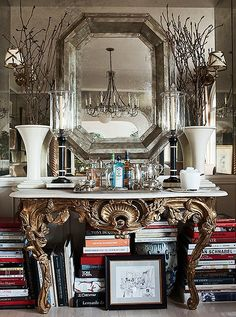 A gilded console at one end of the dining room houses a bar and more of Mark's design books. The hurricane lamps are from his friend John Rosselli's antiques shop. The custom mirror was made from antique glass.
