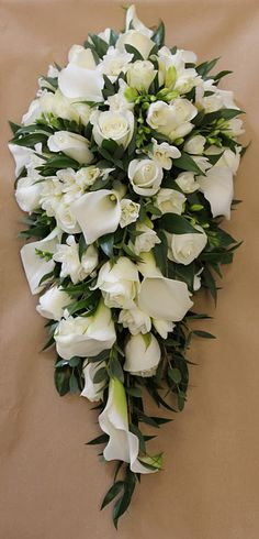 Like this but Maybe a bit smaller A shower/teardrop bouquet of ivory roses, lisianthus and freesia with soft ruscus.