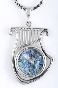 Description: Beautiful Harp Pendant made Of Sterling Silver and set with amazing 2000 Year old Roman Glass. All hand made and no Two are exactly the same!!! Pendant only Chains are available in any size. Comes With an elegant Certificate Of Authenticity. Life Time Guaranty For