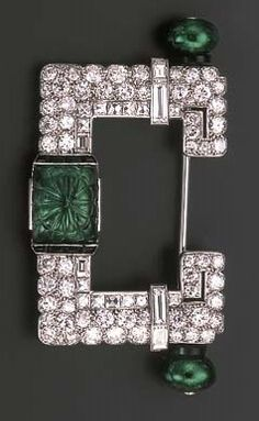 AN ART DECO EMERALD AND DIAMOND BROOCH, BY CARTIER. The central rectangular carved emerald within buff-topped onyx borders to the pavé-set and baguette-cut diamond U-shaped frame with emerald bead and onyx detail to each side, circa 1925, with French assay marks for platinum and gold. Signed Cartier.