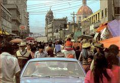"""Mexico City in the 80s. La calle de Santa Escuela, casi llegando al cruce con Manzanares, muy cerca del mercado de La Merced. En esta imagen de los años ochenta, un conductor y su acompañante al atraviesan la multitud que desde hace décadas es cotidiana en esta zona de la ciudad. Al fondo destaca la iglesia de Santa Cruz y Soledad. Imagen del libro """"Historia de la Ciudad de México"""", de Fernando Benítez."""
