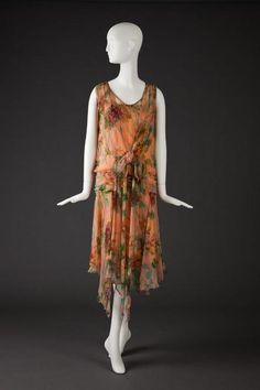 ~Dress 1920's    Sleeveless Dress Extends To Just Below Knee Length With Uneven Hem At Back. Rounded Neckline In Front With No Collar, and Lower Rounded Neckline In Back. Fabric Is Sheer Peach With Yellow, Pink, Red, Purple and Green Floral Pattern. Drop Waist With Wide Gathered Waistband, Back Sash and Bow. Peach Underdress With Sheer Shoulder Straps.  The Goldstein Museum of Design~