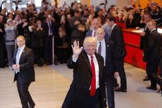 U.S. President elect Donald Trump reacts to a crowd gathered in the lobby of the New York Times building after a meeting in New York