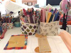 """Cá estou, ilustrando um livro com a técnica de costura e bordado, em meio a muitos tecidos coloridos. Resolvi colocar cada tipo de tecido em um """"pote"""" de pano diferente. Os florais à esquerda e os geométricos à direita. Gosto demais de mexer com isso tudo! E o livro? Logo fica pronto..."""