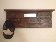Coat/hat hanger made from stained pallet wood, a car mirror, and spray painted bolts.