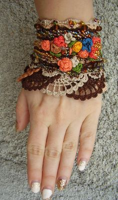 This unique handmade crochet cuff bracelet is made of 100 % cotton thread. There are used different crochet techniques in creating this cuff bracelet. It is a colorful cuff bracelet in ethnic style. The main colors are dark brown; three shades of beige, small roses are in blue, light orange, dark orange, yellow, and green for the small leaves. Multicolor tiny beads are used for decoration. This gorgeous cuff bracelet closes with one square button. This cuff bracelet is a unique handmade…