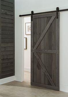 Get a farmhouse look with a barn-style sliding door in your entryway. We created our own using prefinished weathered planks and a sliding barn door hardware kit. Click to learn how.