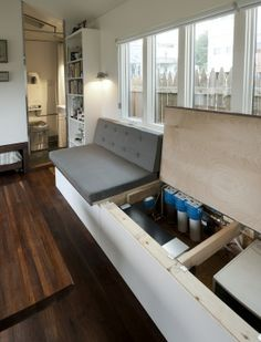 Minim House - The large built-in sofa on the curb side of the home contain a water tank and filtration system. Details on the sight. (MinimHomes.com)