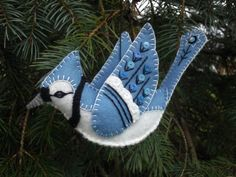 This three-dimensional embroidered blue jay ornament is a true heirloom piece. Made from light blue and soft white wool felt. Details on