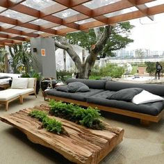 Summer style!! GRAY AND PALE WOOD COVERED OUTDOOR SEATING AREA! Modern contemporary outdoor garden with covered pergola terrace veranda patio deck - gray cushions on the low sofas and a gorgeous very live edge coffee table!! Love how the plants are planted IN the coffee table!!