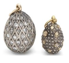 Two jewelled silver and gold miniature pendant eggs.St Petersburg, circa 1890the first enriched with diamond-set trellis, Erik Kollin; the second textured and covered with gold stars, set at intervals with rose-cut diamonds, Alfred Thielemann height of largest