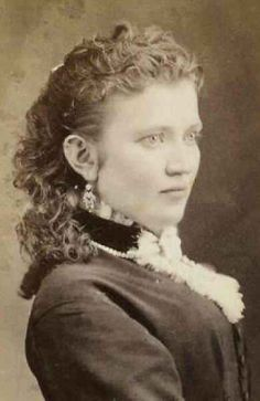 1877. A very simple hairstyle. She looks to have naturally curly hair that is short by Victorian standards.