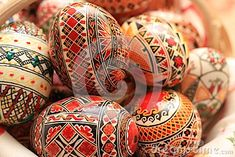 Decorated Easter eggs. Traditional Easter eggs painted with multiple colors. Red, green, blue, brown and black lines, shapes, traditional paintings. The Easter eggs are sitting on a Romanian traditional embroidery towel. Some of the eggs in the background are out of focus.